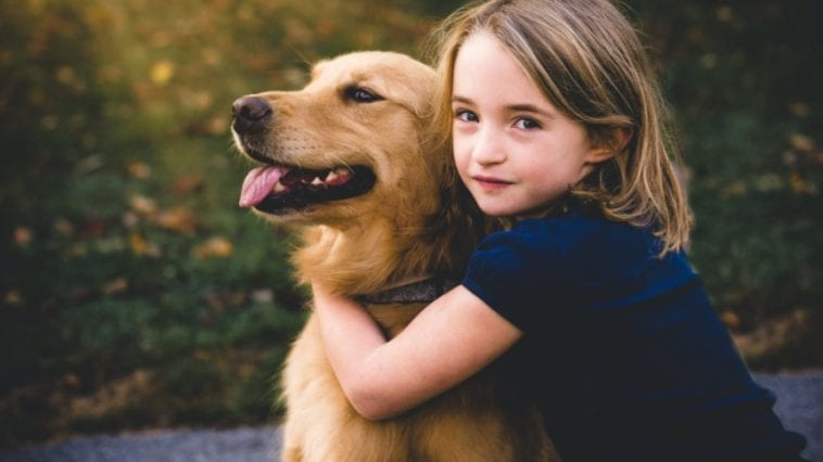 Picture of a child with a dog in order to answer how to convince your parents to get a dog.